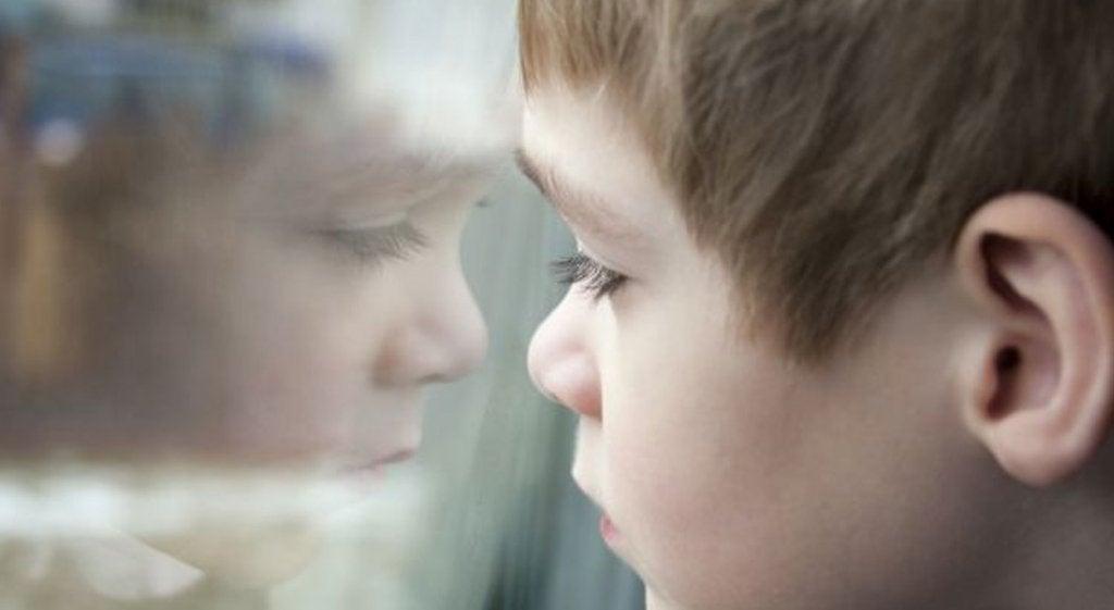Niño mirando tras un cristal representando las futuras causas del narcisismo exagerado