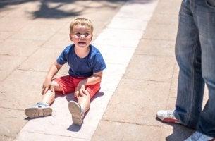 Niño con trastorno de desregulación disruptiva del estado de ánimo en el suelo llorando