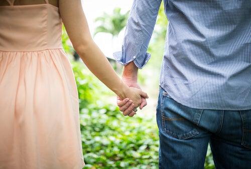 Pareja agarrada de la mano para representar el compromiso en las relaciones