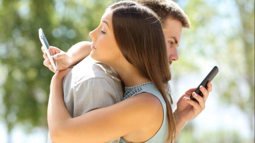 Pareja mirando el móvil mientras se abraza