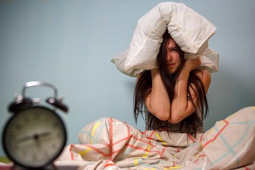 Chica adolescente con almohada en la cabeza mientras suena el despertador
