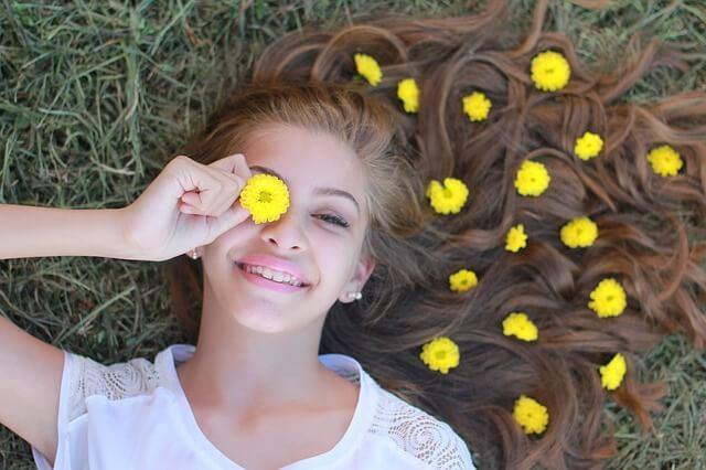 Chica adolescente con flores amarillas