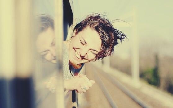 chica asomada a la ventanilla del tren disfrutando de viajar solo