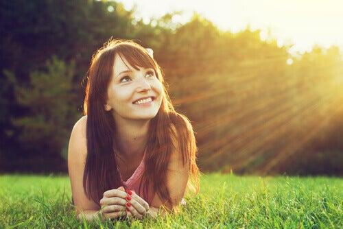 Chica sonriendo mirando al sol y pensando de forma optimista