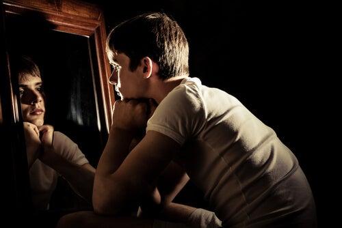 Chico adolescente mirándose al espejo sintiendo emociones extrañas