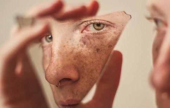 chico sujetando cristal donde se refleja su rostro como resultado de los sesgos cognitivos