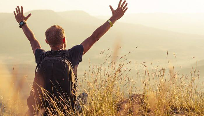 hombre con los brazos extendidos disfrutando de viajar solo