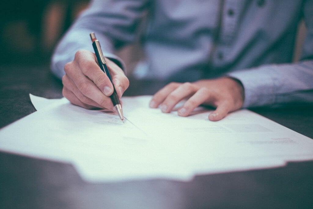 Hombre escribiendo sus propósitos en papel
