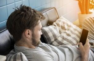 Hombre mirando el móvil mientras practica el sedentarismo