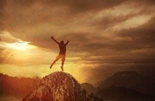 Hombre saltando en la montaña por adicción a la adrenalina