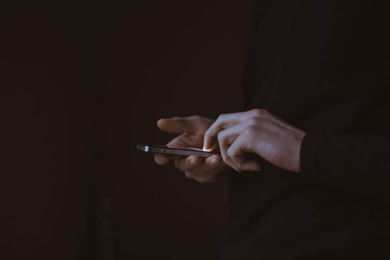 Hombre mirando los mensajes de su móvil sufriendo ciberbullying