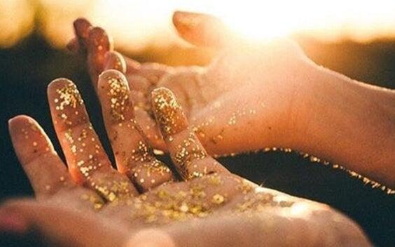 manos con polvo dorado representando el El sentido de la vida según Viktor Frankl