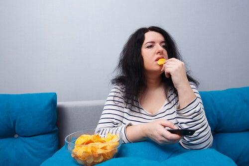 Mujer comiendo patatas mientras ve la televisión
