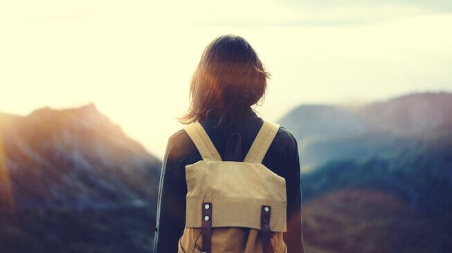 Mujer con mochila ante una montaña