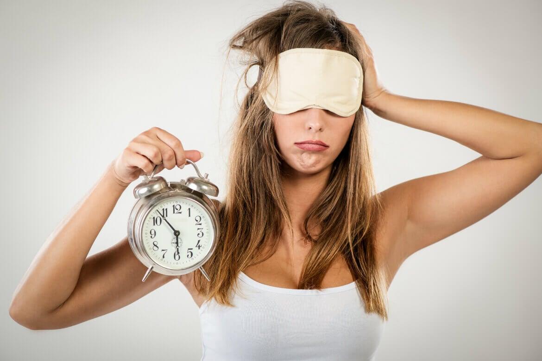 Mujer despierto con un reloj en su mano