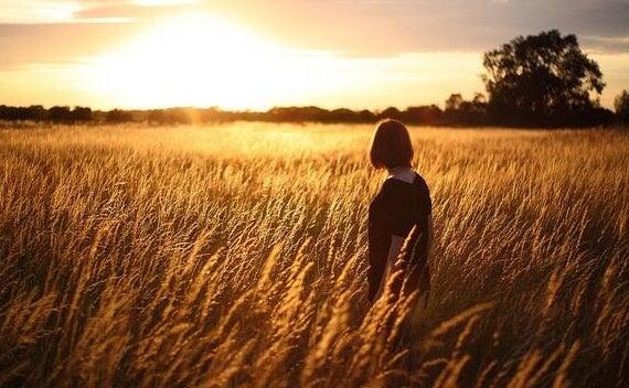 Mujer en campo de trigo pensando en cuidar de sus Glándulas pituitaria y pineal