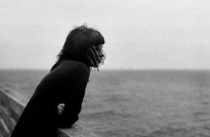 Mujer mirando al mar pensando en decir adiós