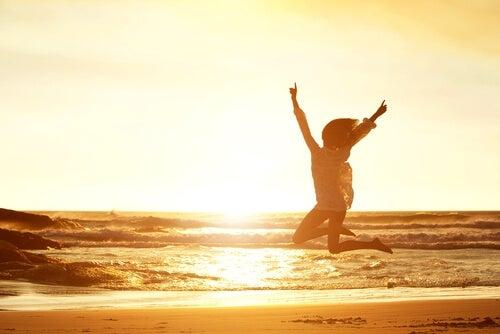 Mujer saltando frente al mar