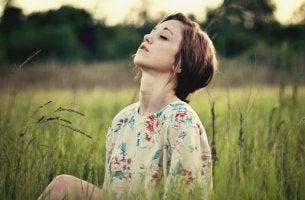 mujer sentada en el campo practicando la mente silenciosa