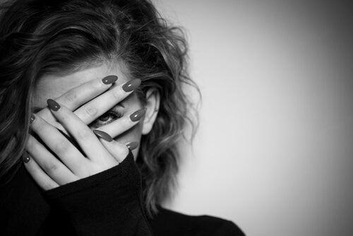 Mujer tapándose la cara por miedo