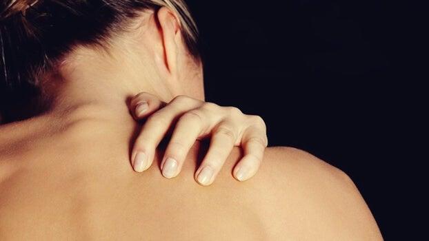 Mujer tocándose la espalda debido a el trastorno por excoriación
