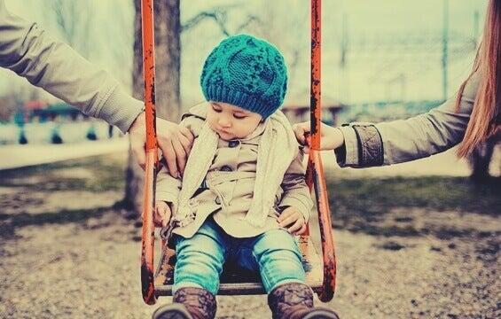 Niño en el columpio con brazos de los padres a los lados