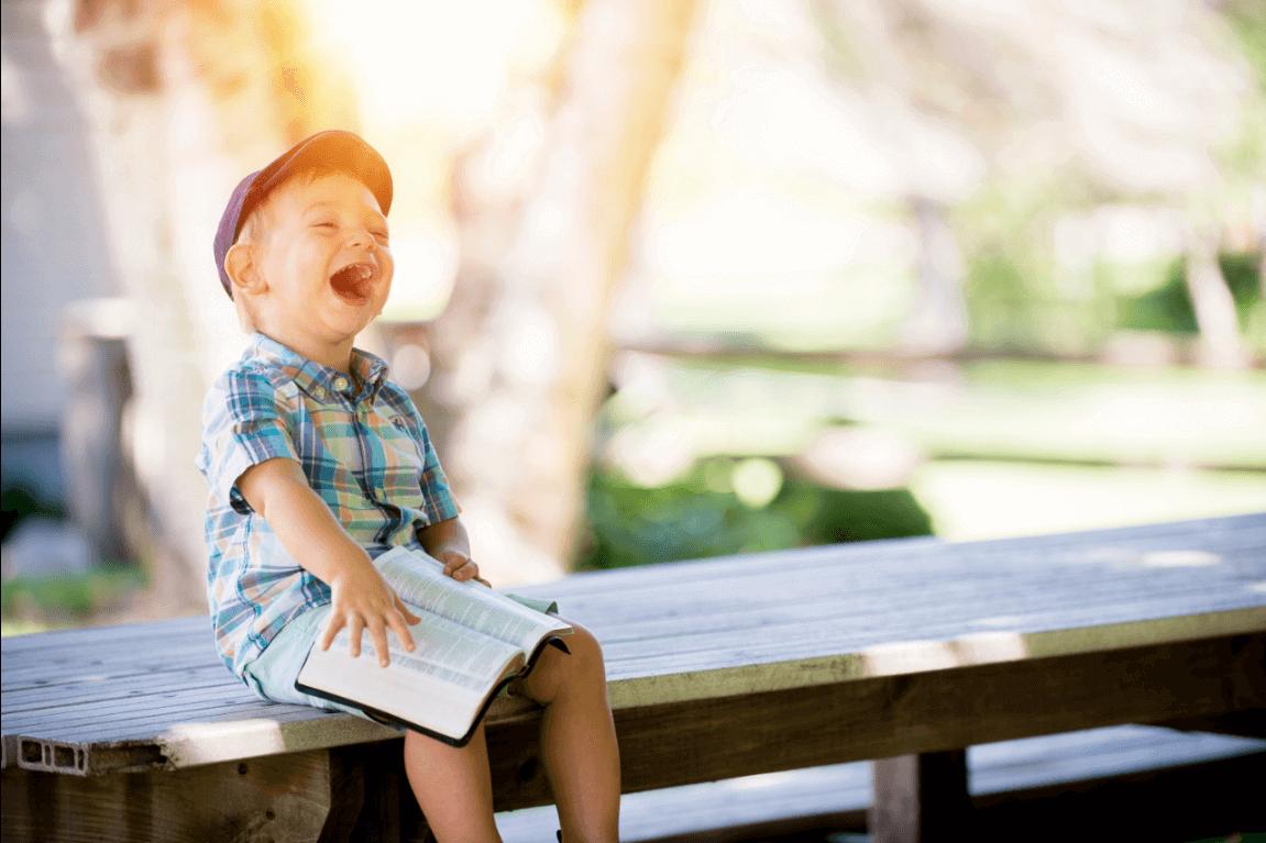 Niño riéndose con un libro