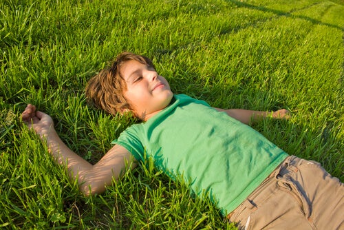 Niño tumbada en el cesped