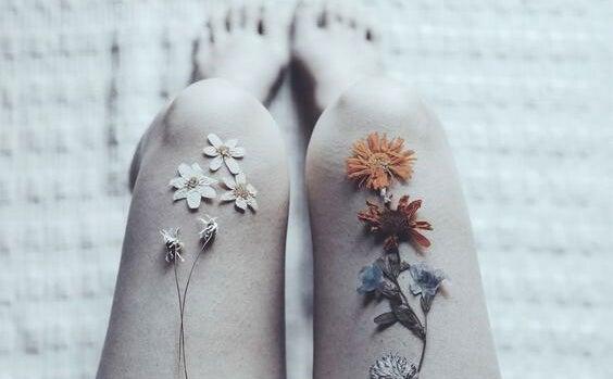 piernas con flores de mujer que sufre problemas emocionales