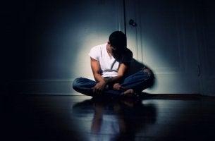 Adolescente sentado en el suelo con el síndrome amotivacional provocado por consumir marihuana