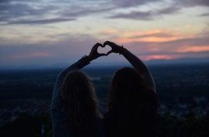 Amigas formando un corazón con sus manos