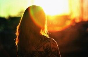 Chica de espaldas viendo el atardecer