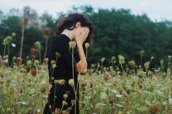 chica tapándose rostro pensando en los ingredientes de la felicidad