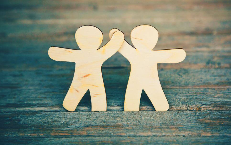 Dos figuras dándose la mano