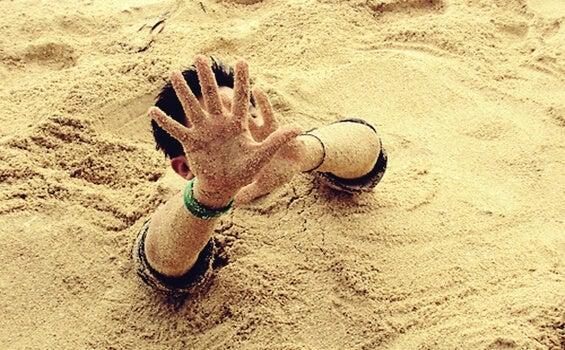 chico hundiéndose en arenas movedizas al no poder gestionar los pensamientos obsesivos