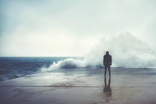 Hombre mirando una ola en el mar pensando en los ingredientes de la felicidad