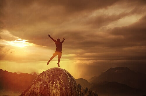 Hombre saltando en la cima de una montaña feliz por aplicar las técnicas de control emocional