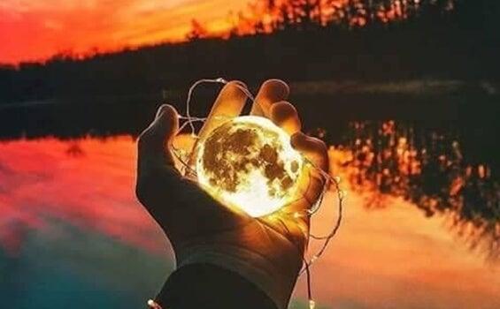 mano sujetando luna que representa las creencias que limitan el crecimiento personal