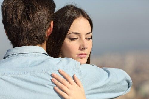 Mujer abrazada a su pareja pensando en otro hombre