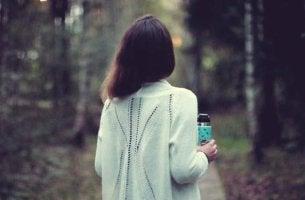 Mujer con vaso en la mano ante un camino preguntándose ¿Debo irme o debo quedarme?