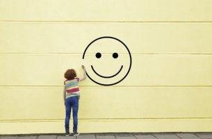 Mujer dibujando una cara feliz para explicar la eudaimonía y hedonismo