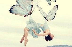 mujer llevada por mariposas intentando sanar heridas
