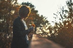 Mujer mirando una flor al atardecer