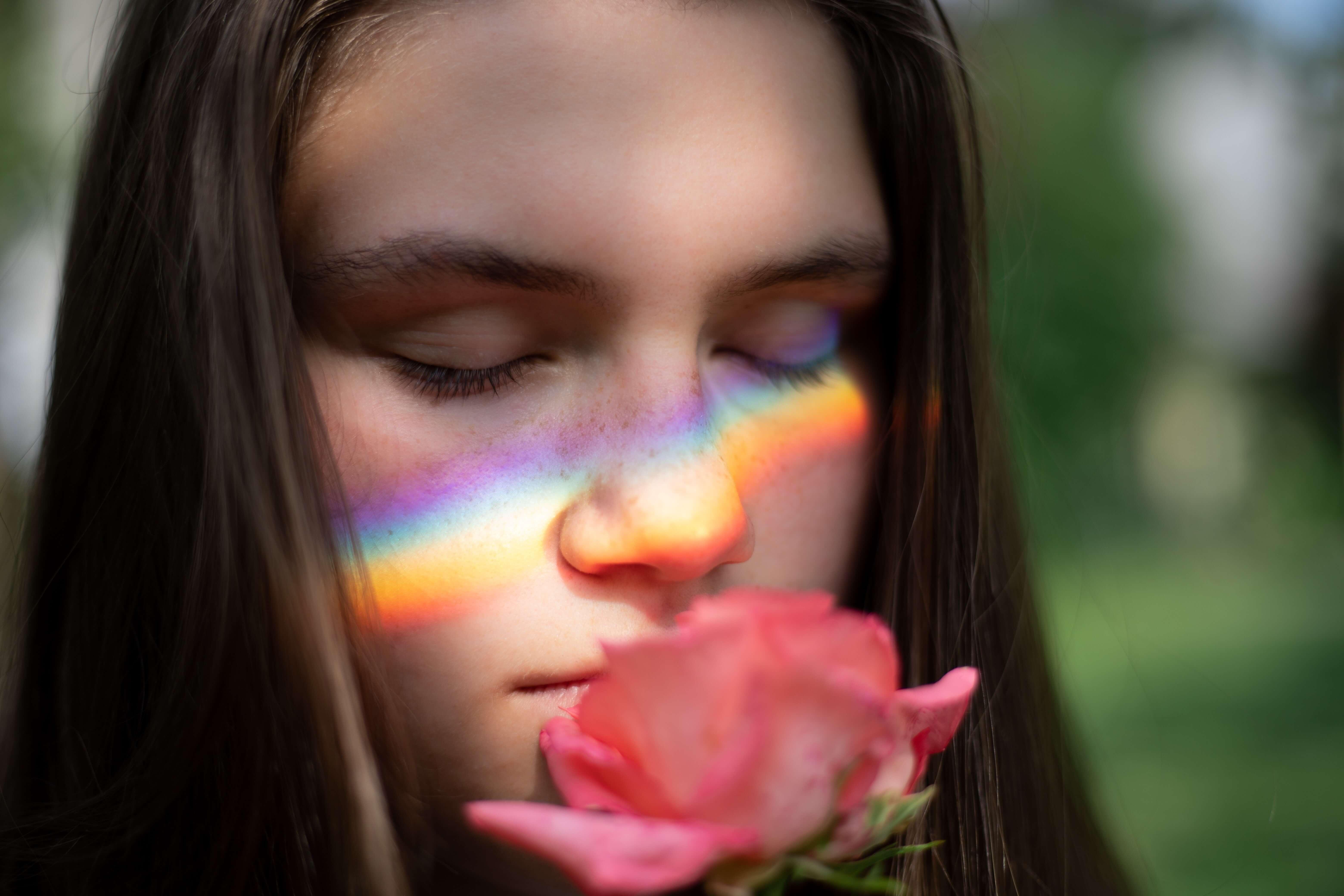 Mujer oliendo una rosa con el reflejo del arco iris en sus mejillas y pensando en los recuerdos del ayer