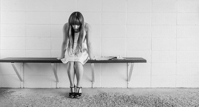 Mujer con depresión psicótica sentada en un banco