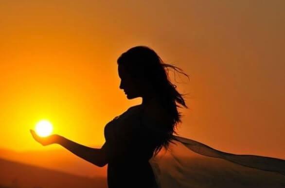 mujer sujetando sol en la mano representando las frases para recuperar la energía positiva