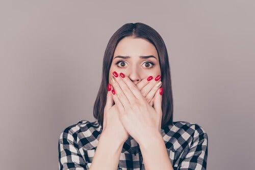 Mujer tapándose la boca mientras piensa en cómo se ve el sexo en la sociedad