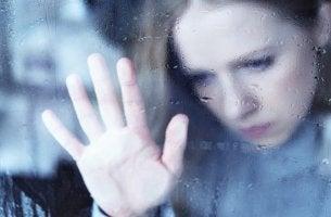 Mujer tras un cristal con lluvia