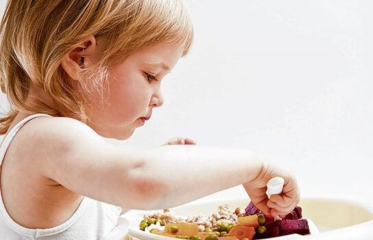 niña comiendo mientras sus padres usan la culpa para educar