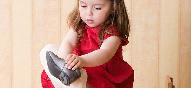 niña autónoma poniendose un zapato y representando las frases de María Montessori